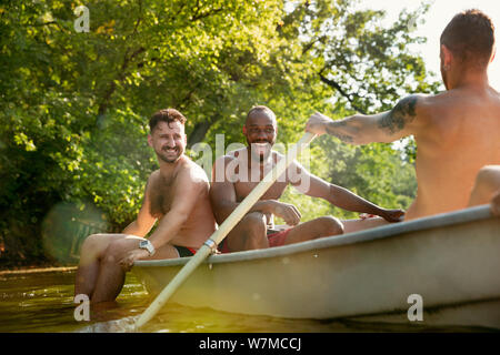 Happy group of friends having fun while laughting, splashing water and swimming in river. Joyful men in swimsuit in a boat at riverside in sunny day. Summertime, friendship, resort, weekend concept. - Stock Photo