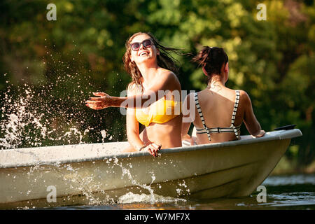 Happy group of friends having fun while laughting, splashing water and swimming in river. Joyful women in swimsuit in a boat at riverside in sunny day. Summertime, friendship, resort, weekend concept. - Stock Photo