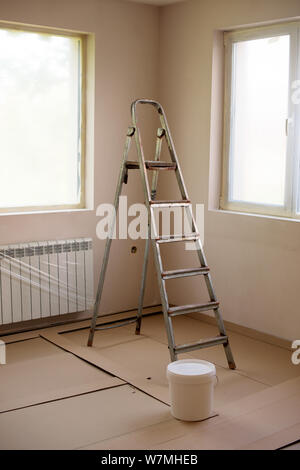 Painting walls in room with roller and ladder during renovation . The windows are packed with nylon. Image - Stock Photo