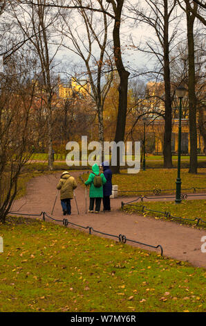 Saint Petersburg, Russia - November 16, 2018: Three seniors engaged in Nordic walking in the Park on a cloudy day in late autumn - Stock Photo