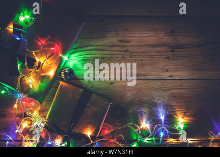 Christmas decorative lights. Christmas garland lights on wood. Colorful Xmas light bulbs on wooden table with copy space. Christmas mood. Free space f - Stock Photo