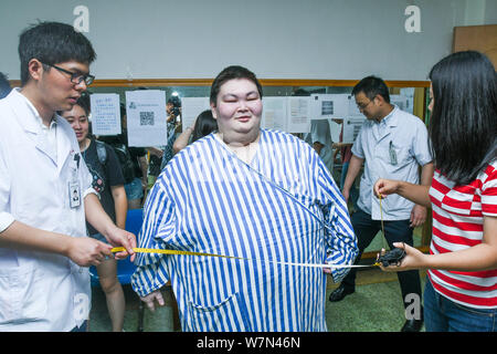The waistline of 26-year-old man Huang Tao (pseudonym), who is believed to be the heaviest man in China, is being measured during a rehabilitation tra - Stock Photo