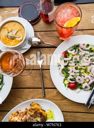 top view of Spicy salad prawn with tomatoes, lettuce, lasagna, sea food Mediterranean soup with noodles, shrimps in white bowl with mug of beer, orang - Stock Photo