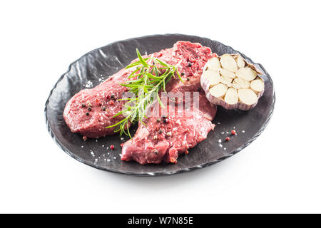 Beef meeat Rib-Eye steak wit rosemary salt and pepper in black plate isolated on white - Stock Photo