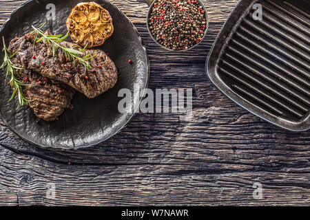 Grilled beef Rib Eye steak with garlic rosemary salt and spices - Stock Photo