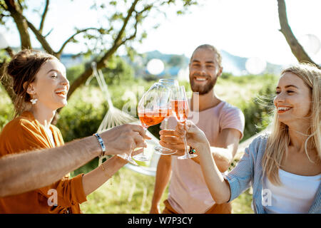 Young and cheerful friends having fun, clinking with wine glasses in the beautifully decorated backyard during a festive meeting or party on a sunny s - Stock Photo