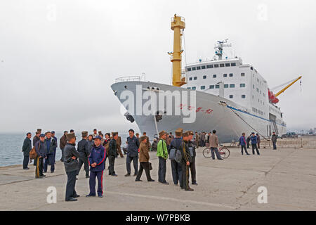 People standing by boat at harbour, East Sea of Korea, Wonsan City, Democratic Peoples' Republic of Korea (DPRK), North Korea 2012 - Stock Photo