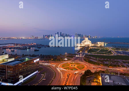 Elevated view at dusk over the Museum of Islamic Art and the Dhow harbour to the modern skyscraper skyline of Doha, Qatar, Arabian Peninsula 2011 - Stock Photo