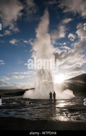 People standing by Strokkur (the Churn) geyser which spouts up to 35 meters erupting every 10 minutes, Golden Circle, Iceland 2006 - Stock Photo