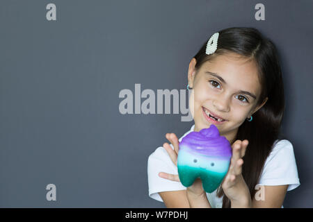little girl without two front teeth laughs while looking at the camera and holding a toy tooth. Lost tooth, loss of milk tooth - Stock Photo
