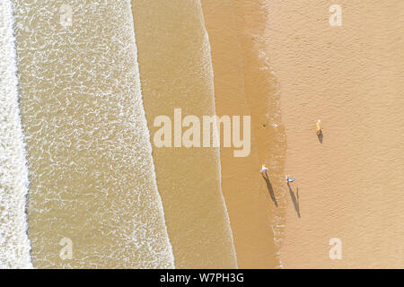 Aerial view of people walking and their shadow on a sand beach next to the waves in Porthcawl Wales UK - Stock Photo
