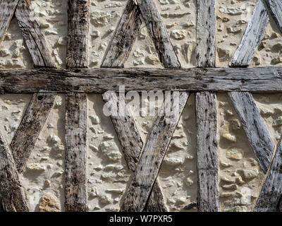 Old wall with exposed timber work and stone infill - France. - Stock Photo