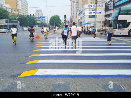 Pedestrians walk on a 3D zebra crossing at Fengtai district in Beijing, China, 27 June 2017.   Photos taken on 27 June 2017 showed a colorful 3D zebra - Stock Photo