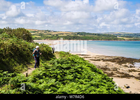 Women walkers hiking on Wales coastal footpath around the bay at Lligwy, Isle of Anglesey, Wales, UK, Britain - Stock Photo