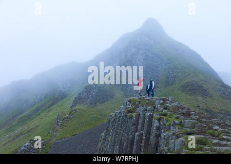 Tourists on Giant's Causeway in the mist, UNESCO World Heritage Site, County Antrim, Northern Ireland, Europe, June 2011. - Stock Photo