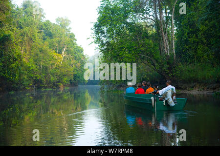 Toursists in a boat moving up the River Kinabatangan through lowland rainforest, Sabah, Malaysia, Borneo. - Stock Photo
