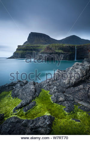 Dramatic coastline and waterfall at Gasadalur on the Island of Vagar, Faroe Islands. June 2012. - Stock Photo