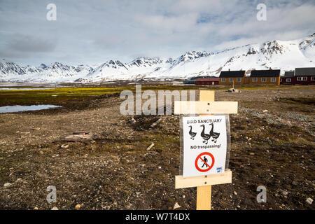 Sign warning of ground nesting birds, Ny-Alesund International Research Village, Spitzbergen, Svalbard, Norway, June, 2012. - Stock Photo