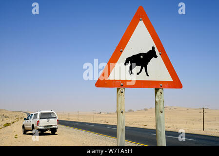 Traffic sign warning of Brown hyaenas (Hyaena brunnea) on a coastal road, Luderitz, Namib desert, Namibia. - Stock Photo