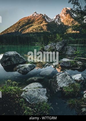Fantastic sunrise at Hintersee lake. Beautiful scene of trees on a rock island during Spring - Stock Photo