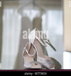 Brides shoes with reflection of dress in the background on her wedding day, bride prep photography - Stock Photo