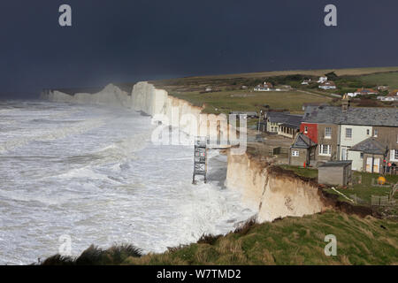 Waves crashing against chalk cliffs, with houses close to edge of cliffs, during a winter storm at Birling Gap, Sussex, England, UK, 15th February 2014. - Stock Photo