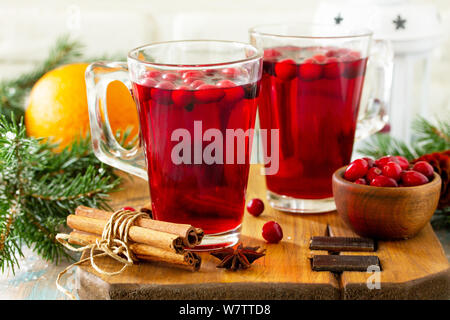 Christmas, Thanksgiving drinks. Hot winter drink with cranberries and cinnamon on wooden table. - Stock Photo