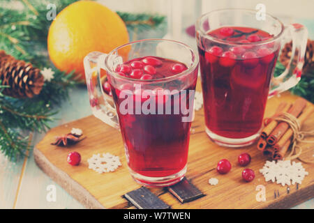 Christmas, Thanksgiving drinks. Hot winter drink with cranberries and cinnamon on wooden table. Toned image. - Stock Photo