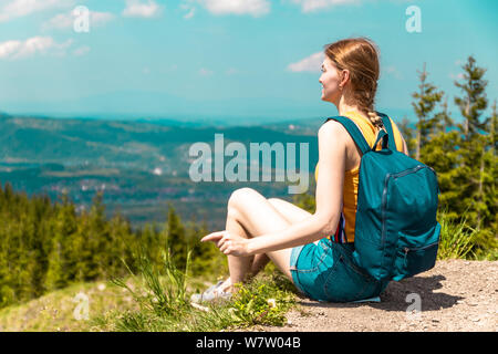 An outraged tired girl with a backpack sits on a mountain and enjoys the beautiful hills of the mountain on a sunny day. - Stock Photo