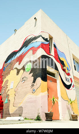 Worm's eye view of a huge colorful graffiti type wall art sign on a building corner at entrance to a nondescript barbershop in Pittsburg, California - Stock Photo