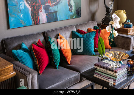 Colourful cushions on grey velvet sofa - Stock Photo