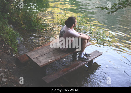 A young man sitting on a flooded wooden bench on a lakeshore. Looking in the distance, contemplating... - Stock Photo
