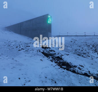 Svalbard Global Seed Vault in mist, with glittering facade designed by artist Dyveke Sanne. Light reflected in steel, mirrors, and prisms in landscape, Svalbard, Norway, October 2012. - Stock Photo