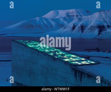 Svalbard Global Seed Vault at twilight, with glittering facade designed by artist Dyveke Sanne. Light reflected in steel, mirrors, and prisms in landscape, Svalbard, Norway, October 2012. - Stock Photo