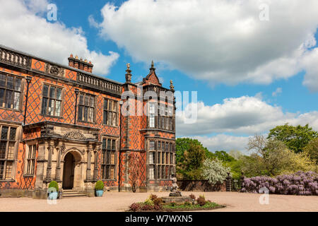 Historic English stately home built in red brick and surrounding park. - Stock Photo