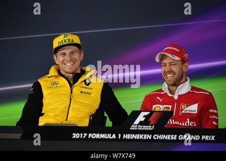 German F1 driver Nico Hulkenberg of Renault, left, and German Formula One driver Sebastian Vettel of Scuderia Ferrari attend a press conference ahead - Stock Photo