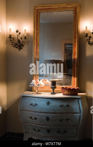 Mirror and lamp on antique drawers - Stock Photo