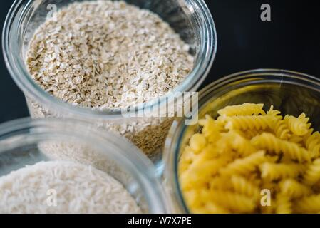 A closeup shot of oats, macaronis and rice in containers - Stock Photo