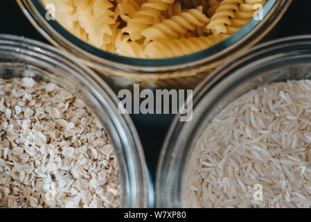An extreme closeup shot of oats, macaronis and rice in glass containers - Stock Photo