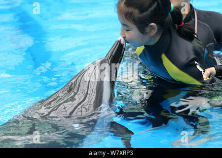 Chinese autistic girl Chenchen interacts with a dolphin under the help of a trainer at Chengdu Haichang Polar Ocean Park in Chengdu city, southwest Ch - Stock Photo