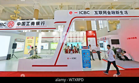 --FILE--A Chinese employee walks past the stand of ICBC (Industrial and Commercial Bank of China) during an exhibition in Beijing, China, 8 September - Stock Photo