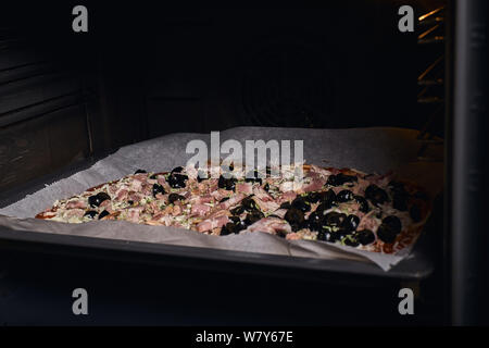 pizza dough with the ingredients before putting in the oven to cook - Stock Photo