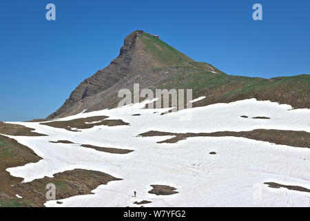 scenic view of swiss alpine mountain faulhorn and snow fields with small distant hiker. Alpine mountain landscape in jungfrau region.