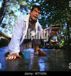 Working on his   Sprinklers and getting splashed in the face - Stock Photo