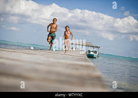 Smiling young girl and her older brother running along a wooden jetty in their swimwear. - Stock Photo