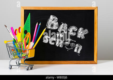 Various colorful school supplies and shopping trolley on the background of the school board with the words back to school - Stock Photo