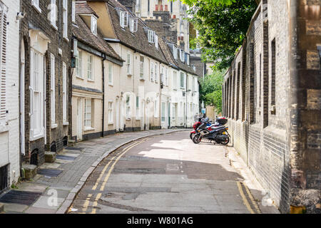 Bicycles and Scooters are parked outside terraced houses along the narrow street, Cambridge, England, UK Stock Photo