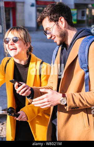 Young mixed race couple using phone on street - Stock Photo
