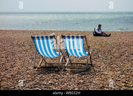 Two blue and white striped deckchairs on pebble beach with person in background, Brighton, East Sussex UK - Stock Photo