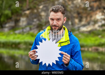 An impudent young man is holding a card blank for your advertisement in his hands, he is standing on a blurred natural landscape. - Stock Photo